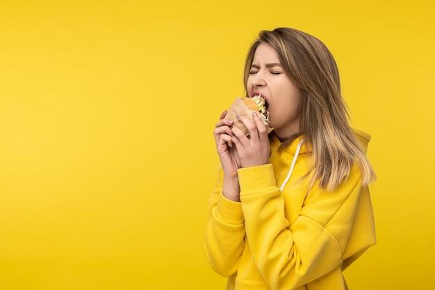 Фотография привлекательной дамы позирует, сильно кусая бургер. носит повседневную желтую толстовку с капюшоном на изолированном желтом фоне.