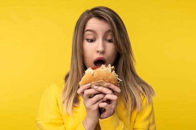 Фотография привлекательной дамы, удивленно позирующей, пытается откусить гамбургер. носит повседневную желтую толстовку с капюшоном на изолированном желтом фоне.