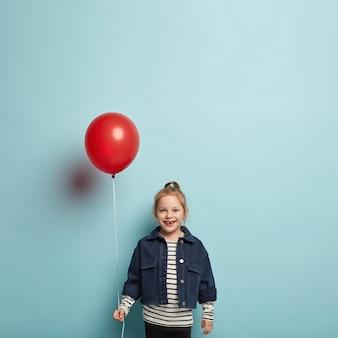 행복한 넓은 미소를 지닌 매력적인 어린 아이의 사진, 축제 분위기에있는 유행 데님 재킷을 입은 공기 풍선을 들고 엄마를 축하하고 싶어합니다.