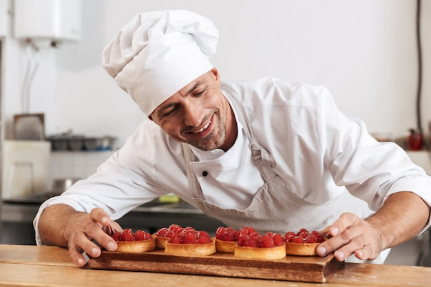 케이크와 함께 접시를 들고 흰색 제복을 입은 매력적인 남성 최고 사진