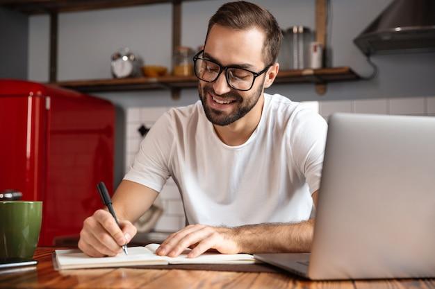 Фотография привлекательного мужчины 30 лет в очках, записывающего заметки во время использования серебряного ноутбука на кухонном столе