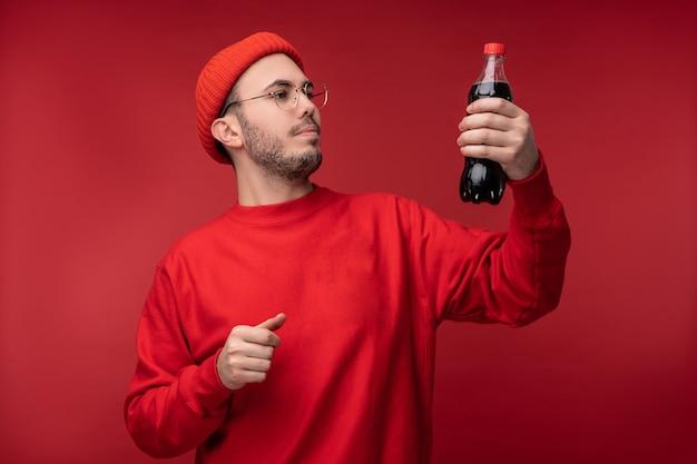안경 및 빨간 옷에 수염을 가진 매력적인 남자의 사진. 행복 한 사람이 음료를 보유 하 고 빨간색 배경 위에 절연 그것을 탐험합니다.