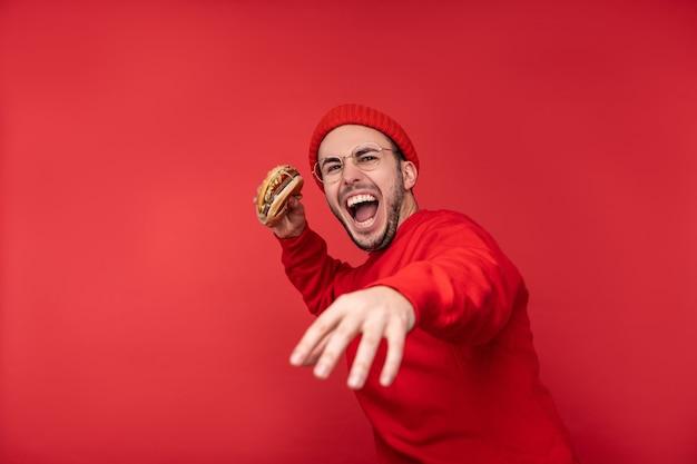 안경 및 빨간 옷에 수염을 가진 매력적인 남자의 사진. 남성은 햄버거를 보유하고 빨간색 배경 위에 절연 그것을 던질 것입니다.