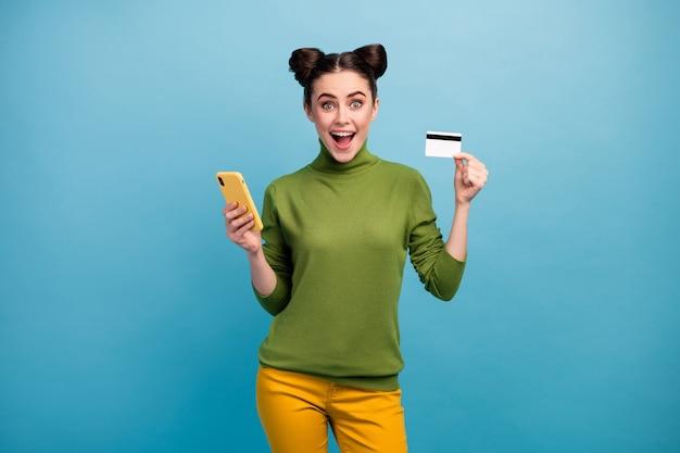 Фотография привлекательной женщины-миллениала с телефоном и пластиковой кредитной картой, советующей новую услугу онлайн-платежей, носить зеленую водолазку, желтые брюки, изолированные на стене синего цвета