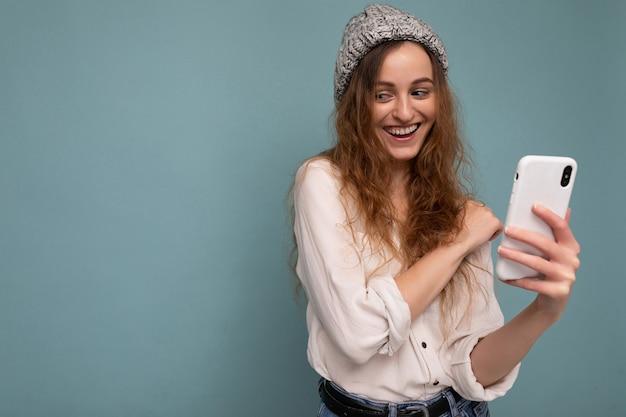 カジュアルな白いシャツと灰色の帽子を着ている魅力的なポジティブな若いブロンドの巻き毛の女性の写真