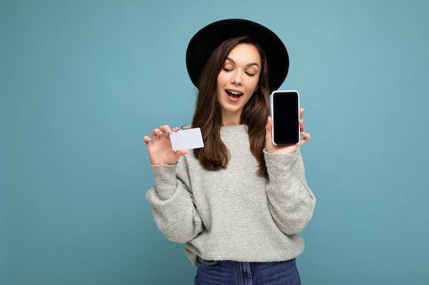 Фотография привлекательной позитивной молодой брюнетки в черной шляпе и сером свитере, изолированных на