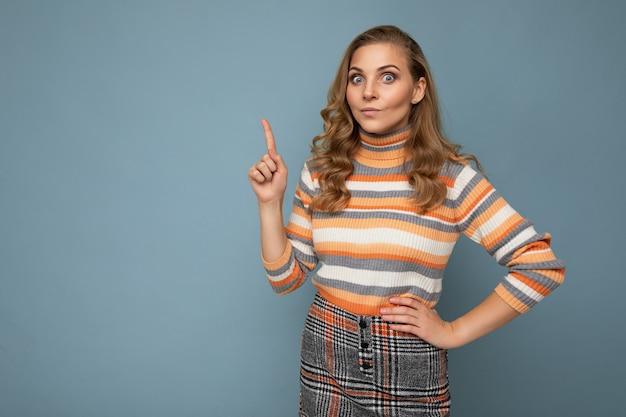 Фотография привлекательной позитивной молодой женщины, указывающей пальцем вверх на copyspace, представляющей рекламное промо с вау, боже, искренними эмоциями, одетая в красивую одежду, изолированную над стеной со свободным пространством.
