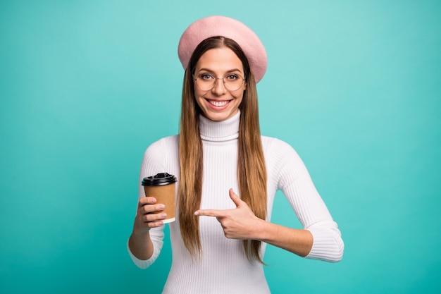 Фотография привлекательной симпатичной леди с хорошим настроением, подержать кофе, чтобы пойти в магазин, прямой палец, советующий вкусовые характеристики, современный розовый берет, белая водолазка, изолированный яркий бирюзовый цвет фона