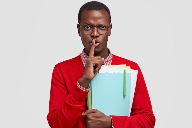 На фото привлекательный тайный мужчина держит указательный палец, демонстрирует жест молчания, несет бумаги ручкой