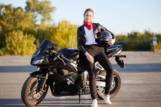 Фотография привлекательной стройной девушки с понитейлом, стоящей возле черного скоростного мотобайка со шлемом в руке, в стильной одежде