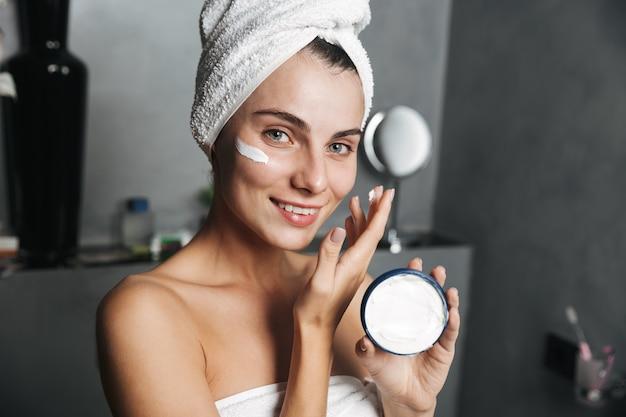 얼굴에 크림을 적용하는 수건에 싸여 매력적인 여자의 사진
