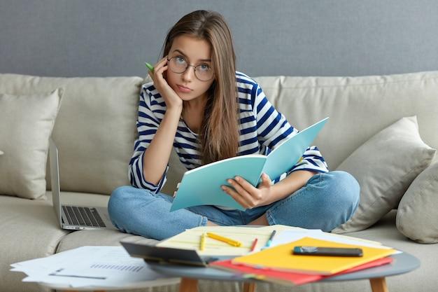 魅力的な女性の写真は、記事を書き、スタートアッププロジェクトを開発し、快適さを楽しみ、ラップトップコンピューターを備えたソファのリビングルームでポーズをとり、足を組んで座り、丸い眼鏡をかけ、真面目な顔つきをしています