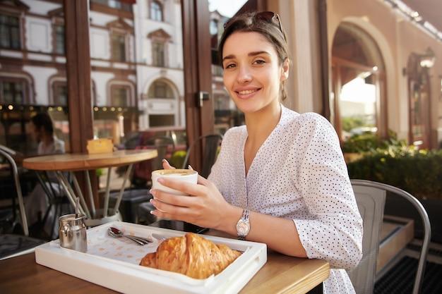 魅力的な若いブルネットの女性の写真彼女の頭にサングラスをかけて夏のテラスで朝食をとり、上げられた手でコーヒーを保ち、広く笑っている