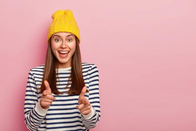 매력적인 젊은 여성 무델의 사진은 손가락 총 제스처를 만들고, 노란색 모자와 줄무늬 점퍼를 착용하고, 선택을 표현하고, 분홍색 배경 위에 고립 된 그녀의 팀에 당신을 선택합니다.
