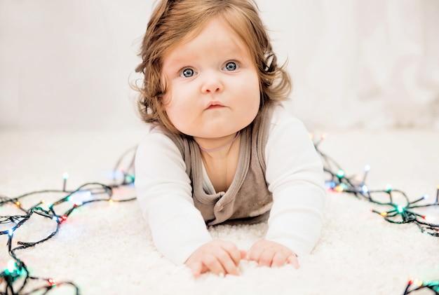 Фото малыша в новогодних огоньках на ковре