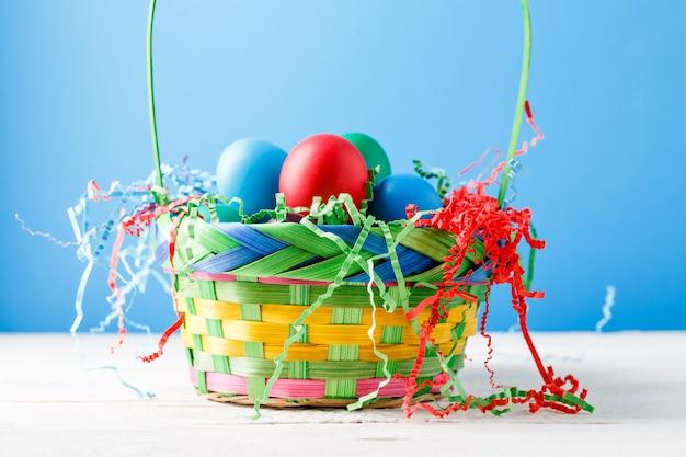 青い空の壁にカラフルな卵とバスケットの写真