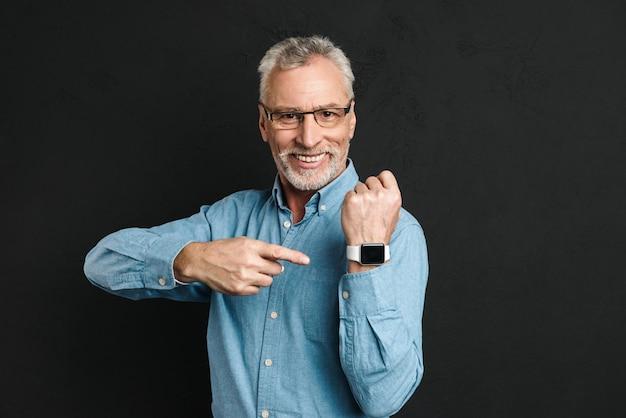 灰色の髪と眼鏡をかけて笑顔と黒い壁に分離された彼の腕時計で指を指すひげを生やした紳士60年代の写真