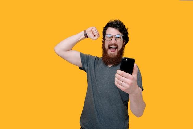Фотография бородатого парня, держащего mobioe и празднующего с поднятой рукой на желтом