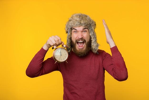 Фотография бородатого парня в уютной зимней шапке, держа часы, крайний срок, чувство спешки и стресса, стоя на желтом фоне