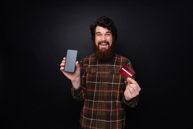 셔츠를 입은 수염 난 남자의 사진, 카메라 스마트폰과 신용 카드를 보여주는, 어두운 벽 위에 서 있는