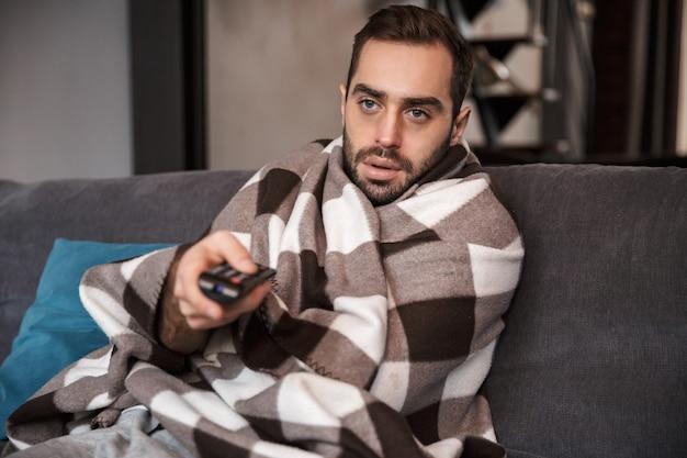 수염을 기른 남자 30 대의 사진은 집에서 소파에 담요에 싸여 앉아있는 동안 온도가 높고 아프다.