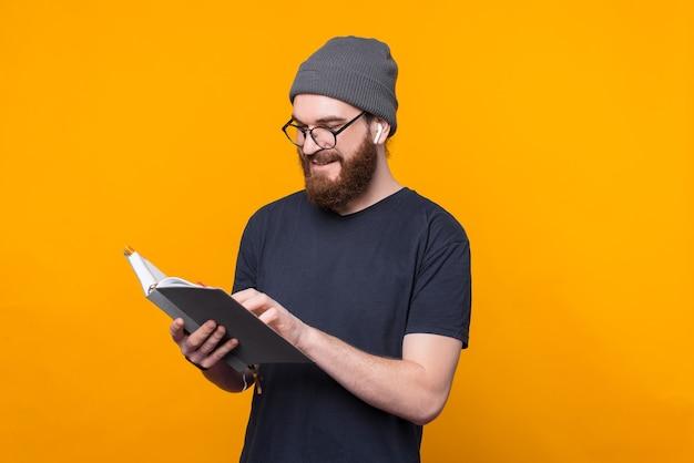 Фотография бородатого мужчины проверяет свой планировщик над желтой стеной