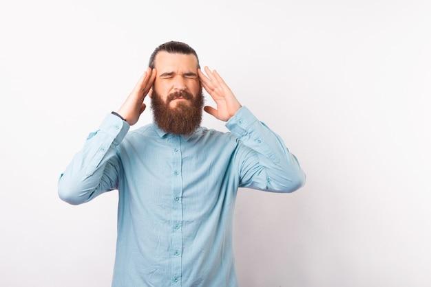 Фотография бородатого мужчины в синей рубашке, страдающего мигренью, тяжелой офисной работой