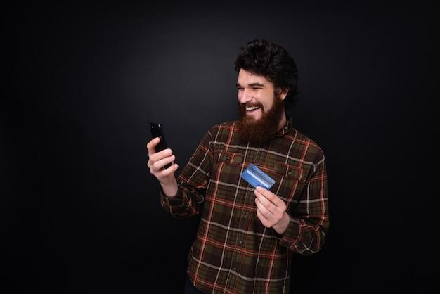 스마트폰과 신용 카드를 들고 갈색 셔츠에 수염 난된 남자의 사진