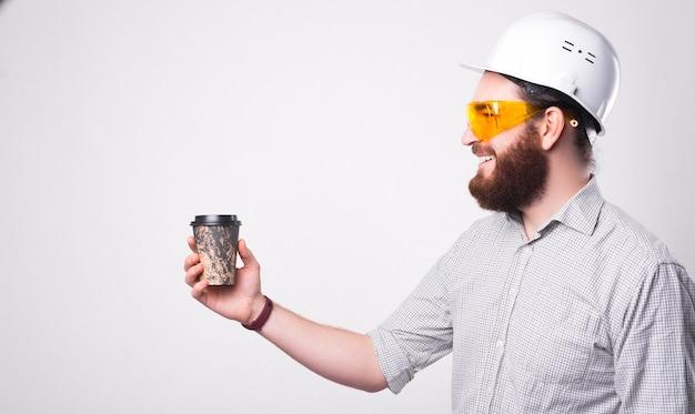 Фотография бородатого работника в белом шлеме, который дает кому-то чашку кофе на вынос