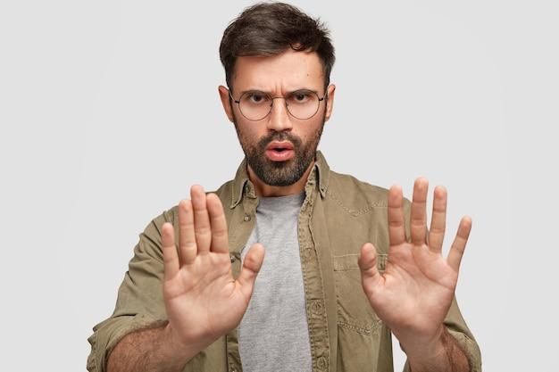あごひげを生やした若い男性の写真は、ジェスチャーを停止し、表情を不快にし、何かを否定し、禁じられていることについて話し、ファッショナブルなシャツを着て、白い壁に隔離されています