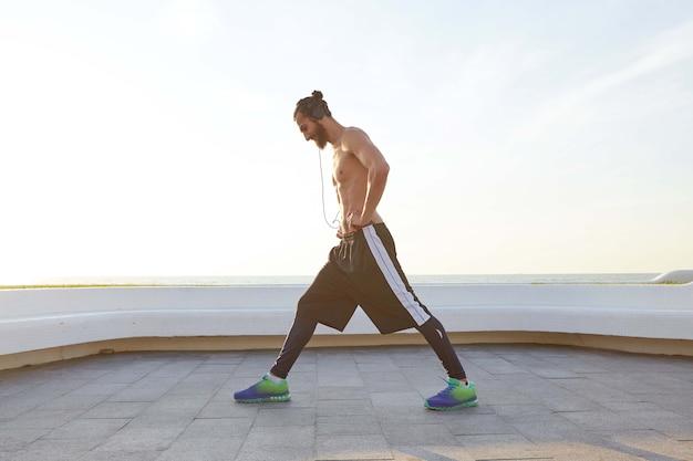 На фото молодой бородатый мужчина с подтянутым спортивным телом, делает упражнения на растяжку, слушает музыку в наушниках, имеет мускулистую форму тела.
