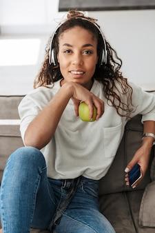 明るいアパートのソファに座って携帯電話を使用して、ヘッドフォンを身に着けている美しいアフリカ系アメリカ人女性の写真