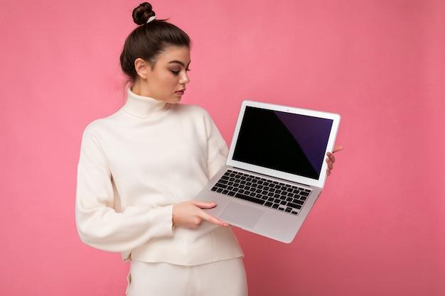 Фотография красивой брюнетки молодой женщины с собранными темными волосами в белом свитере, держащего компьютерный ноутбук и смотрящего на нетбук, изолированном на розовом стенном фоне.