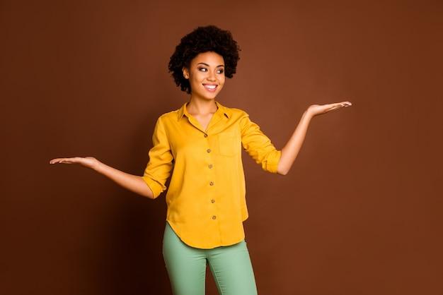 Фото красивой деловой темнокожей кудрявой дамы с открытыми ладонями предпочитают один лучший вариант скидка новинки в желтой рубашке зеленые брюки изолированы коричневого цвета
