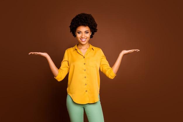 Фото красивый бизнес темная кожа кудрявая дама надежный работник с открытыми ладонями скидка новинка продукты носить желтую рубашку зеленые брюки изолированные коричневый цвет