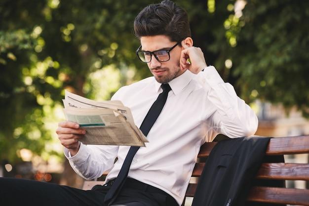 緑豊かな公園のベンチに座って、晴れた日に新聞を読んでスーツを着た美しいビジネスマンの写真