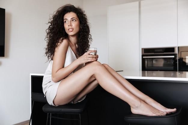 Фотография красивой сконцентрированной женщины в домашней одежде, смотрящей в сторону, сидя в кресле дома и держа стакан воды