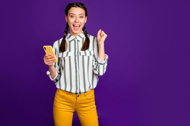 Фотография красивой сумасшедшей дамы, держащей телефонный пост для чтения, положительные хорошие комментарии и лайки, которые празднуют носить полосатую рубашку, желтые брюки, изолированный фиолетовый цвет фона