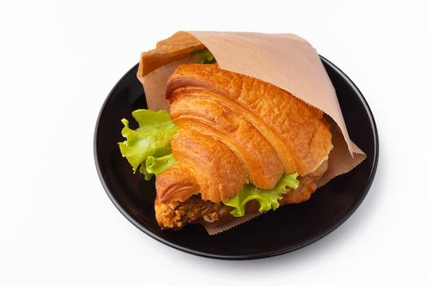 Фото красивых круассанов с курицей и свежим листом салата в черной тарелке на белой поверхности