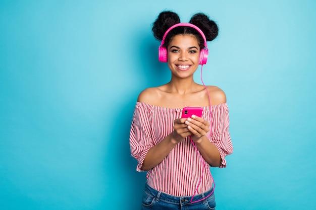 아름 다운 어두운 피부 레이디 보류 전화의 사진 음악 듣기 현대 기술 이어폰 청소년 새 노래 착용 빨간색 흰색 줄무늬 셔츠 알몸 어깨 절연 파란색 벽