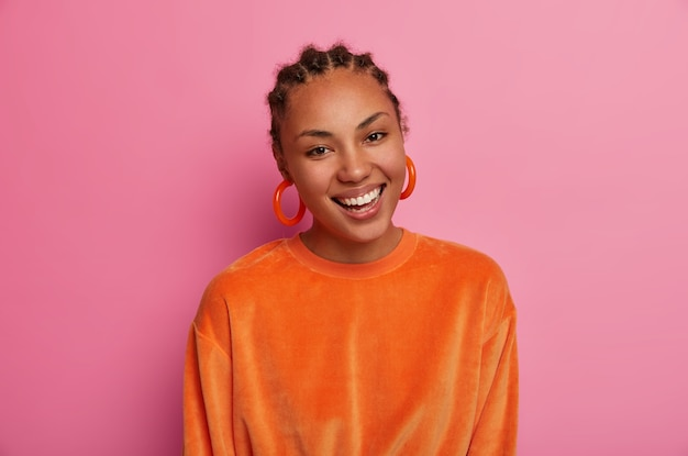 아름다운 우아한 여성의 사진은 긍정적으로 미소 짓고 하얀 치아를 보여주고 평온함을 느끼며 자유 시간을 즐기고 행복을 표현하며 큰 귀걸이와 주황색 스웨터를 입고 쇼핑을 한 후 기뻤습니다.