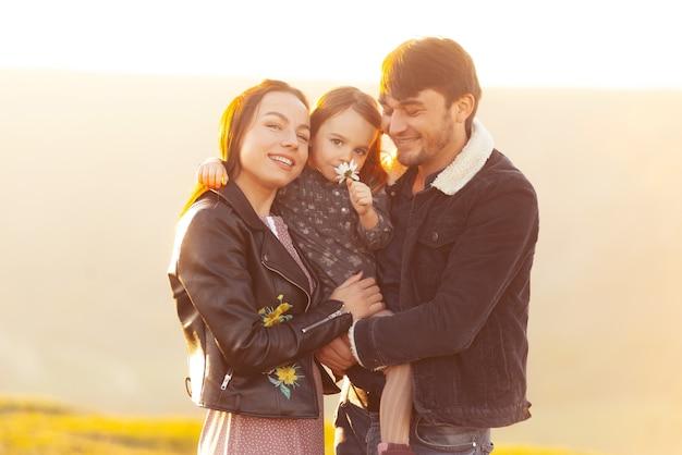 屋外で楽しんで、日没時に抱きしめる美しい家族の写真