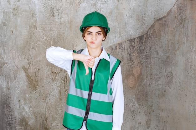 親指を下に与える緑のヘルメットの美しい女性建築家の写真
