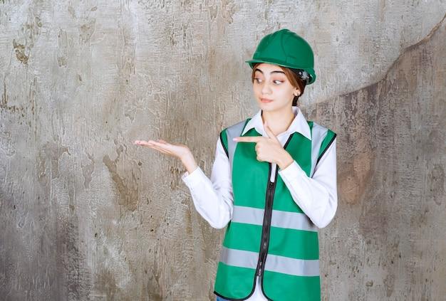 緑のヘルメットを指す美しい女性建築家の写真