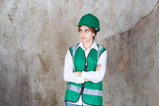 大理石の上にポーズをとって緑のヘルメットの美しい女性建築家の写真