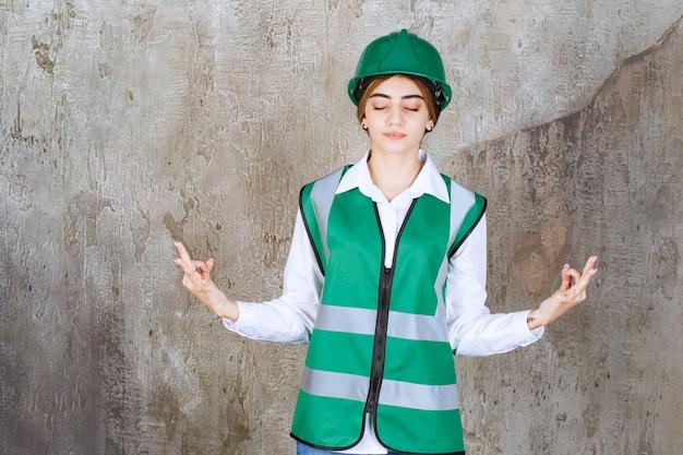 大理石の上に立っている緑のヘルメットの美しい女性建築家の写真