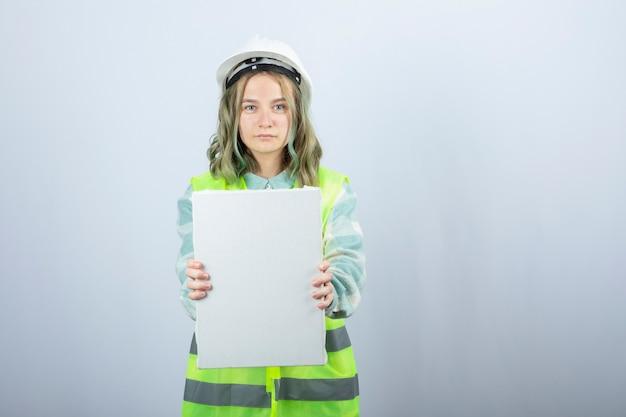 白い壁に空のキャンバスを保持している美しい女性エンジニアの写真。高品質の写真