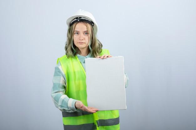 흰 벽에 빈 캔버스를 들고 아름 다운 여성 엔지니어의 사진. 고품질 사진