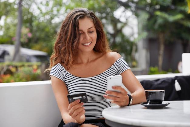 Фотография красивой туристки использует современный телефон и кредитную карту для бронирования билетов онлайн.