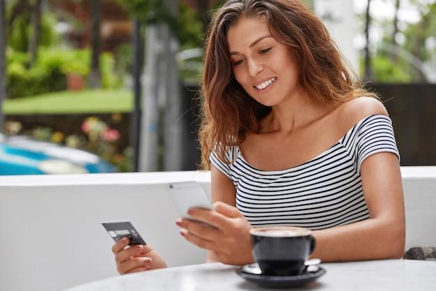 아름다운 여성 관광객의 사진은 온라인 티켓 예약을 위해 현대적인 전화와 신용 카드를 사용합니다.